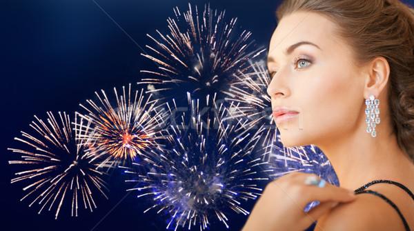 beautiful woman with diamond earring over firework Stock photo © dolgachov