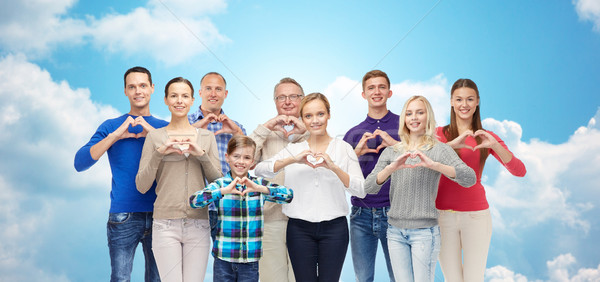 people showing heart hand sign over sky and clouds Stock photo © dolgachov