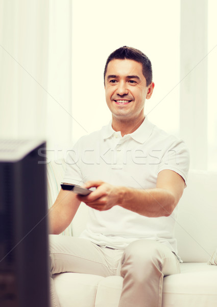 smiling man with remote control watching tv Stock photo © dolgachov