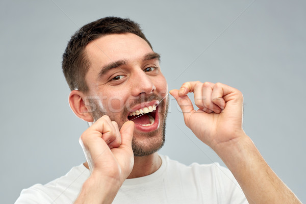 man with dental floss cleaning teeth over gray Stock photo © dolgachov