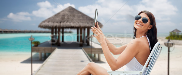 smiling woman with tablet pc sunbathing on beach Stock photo © dolgachov