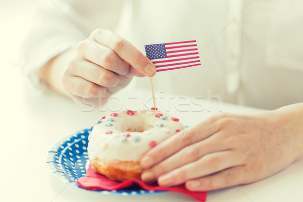 female hands decorating donut with american flag Stock photo © dolgachov