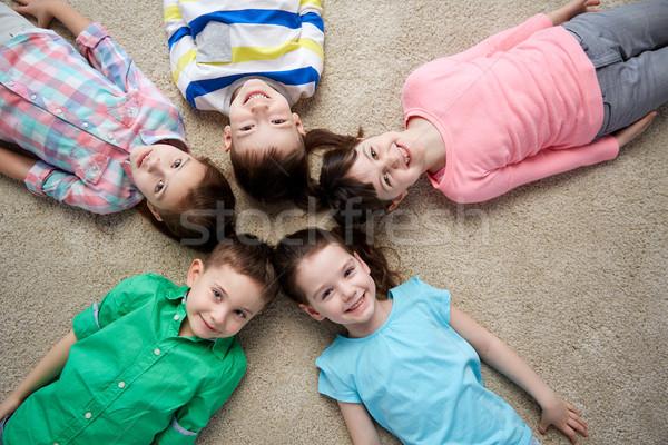 happy smiling little children lying on floor Stock photo © dolgachov