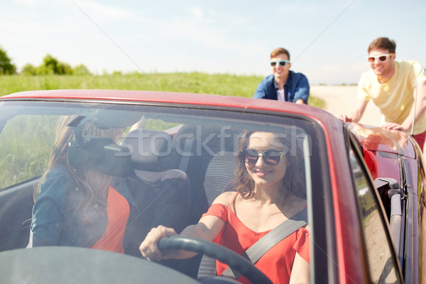 Feliz amigos empujando roto cabriolé coche Foto stock © dolgachov