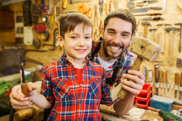 boy with dad holding chisel and hammer at workshop Stock photo © dolgachov