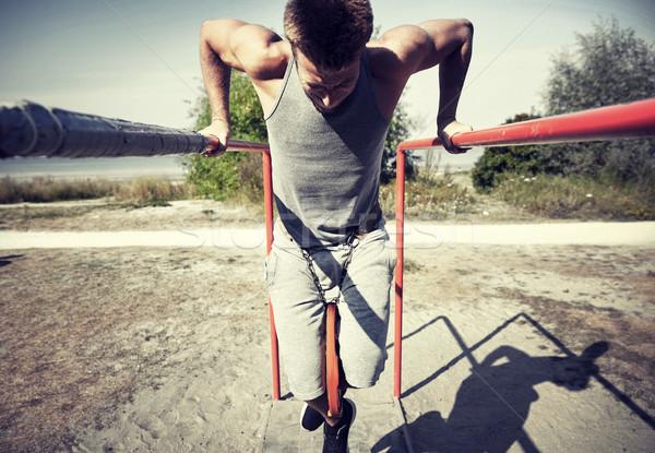 Fiatalember testmozgás párhuzamos rácsok kint fitnessz Stock fotó © dolgachov