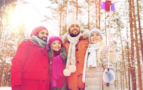 Uśmiechnięty znajomych smartphone zimą lasu technologii Zdjęcia stock © dolgachov