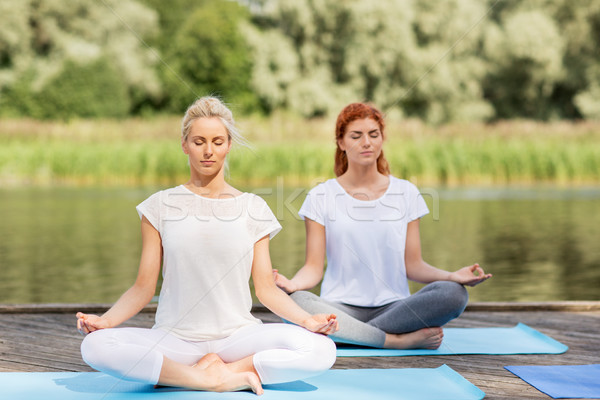 women meditating in yoga lotus pose outdoors Stock photo © dolgachov