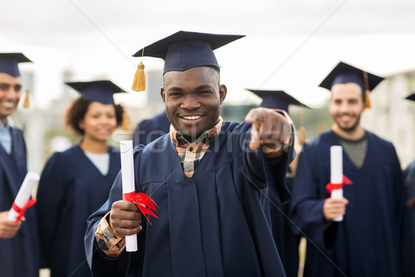 happy student with diploma pointing finger at you Stock photo © dolgachov