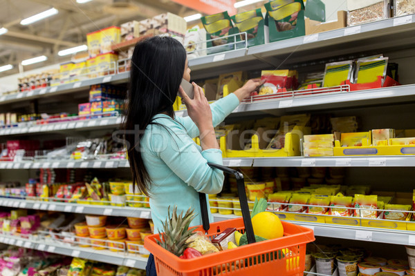 woman with food basket and smartphone at store Stock photo © dolgachov