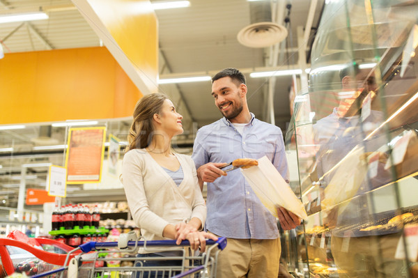 happy couple with shopping cart at grocery store Stock photo © dolgachov