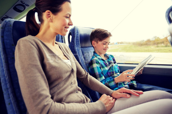 happy family with tablet pc sitting in travel bus Stock photo © dolgachov