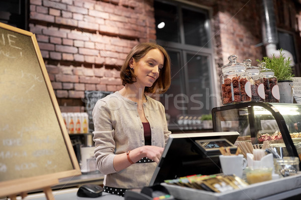 happy woman or barmaid with cashbox at cafe Stock photo © dolgachov