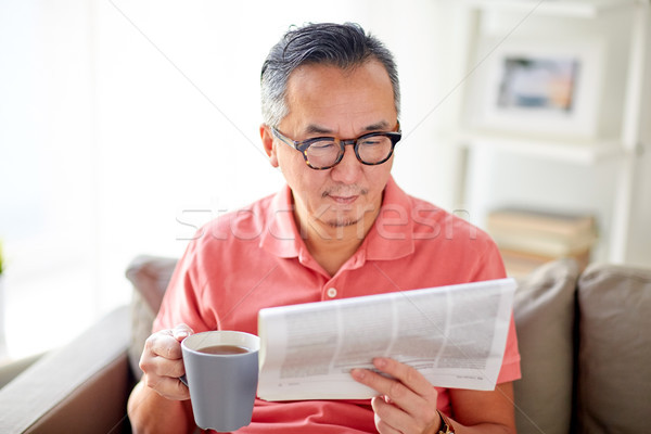 man drinking tea and reading newspaper at home Stock photo © dolgachov