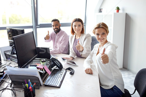 business team showing thumbs up at office Stock photo © dolgachov