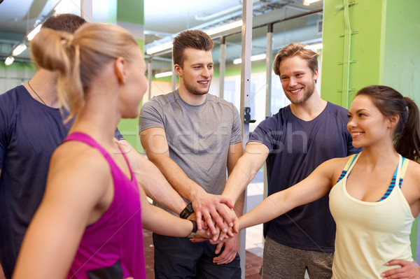 group of friends holding hands together in gym Stock photo © dolgachov