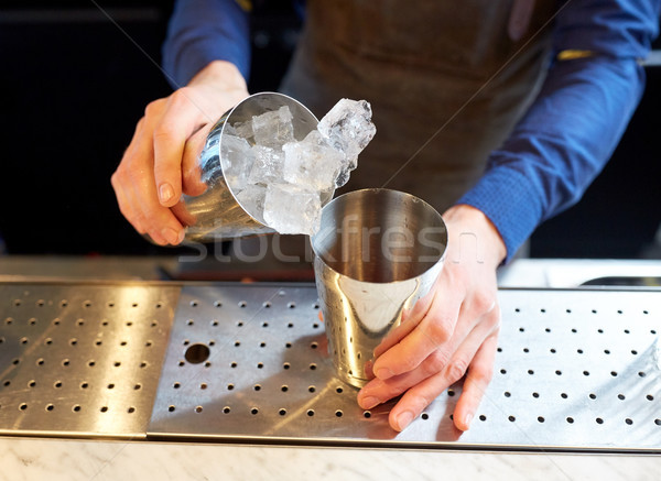 bartender with ice and shaker at cocktail bar Stock photo © dolgachov