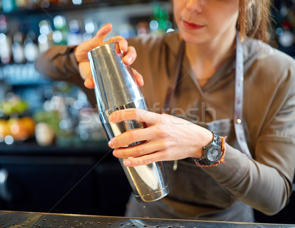 close up of bartender with cocktail shaker at bar Stock photo © dolgachov
