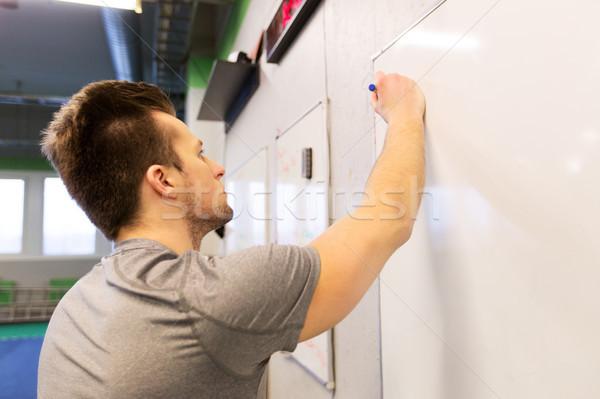 man writing note to whiteboard in gym Stock photo © dolgachov