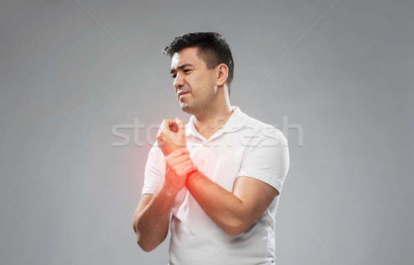 unhappy man suffering from pain in hand Stock photo © dolgachov