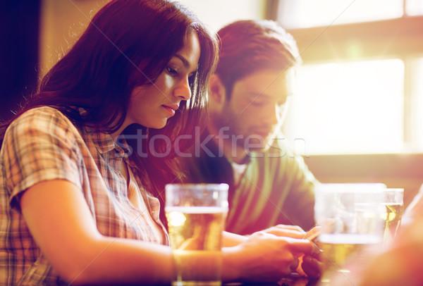 Amigos smartphones potable cerveza pub personas Foto stock © dolgachov