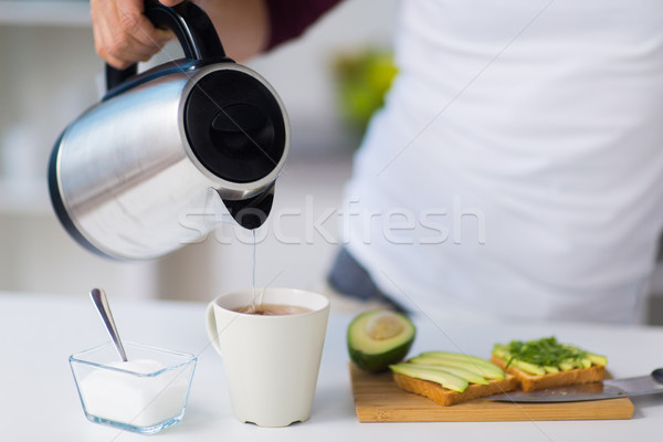 man with kettle making tea for breakfast at home Stock photo © dolgachov