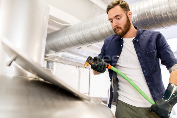 man with hose working at craft beer brewery kettle Stock photo © dolgachov