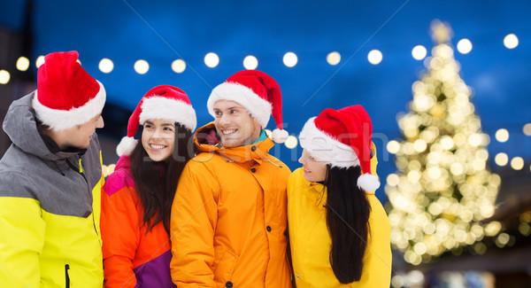 friends in santa hats and ski suits at christmas Stock photo © dolgachov