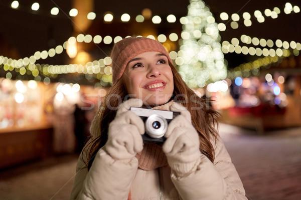 happy young woman with camera at christmas market Stock photo © dolgachov