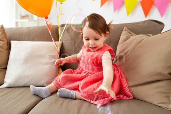 baby girl with soap bubbles on birthday party Stock photo © dolgachov