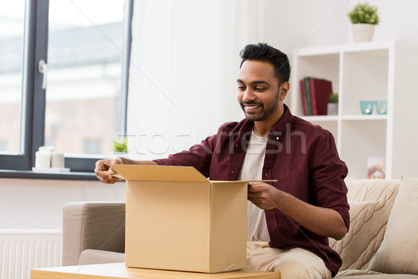 happy man opening parcel box at home Stock photo © dolgachov