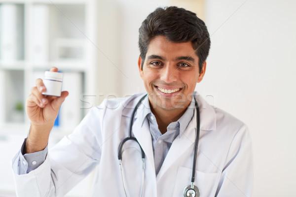 happy doctor with stethoscope and medication Stock photo © dolgachov