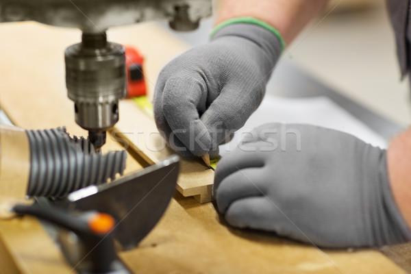 carpenter with ruler measuring board at workshop Stock photo © dolgachov