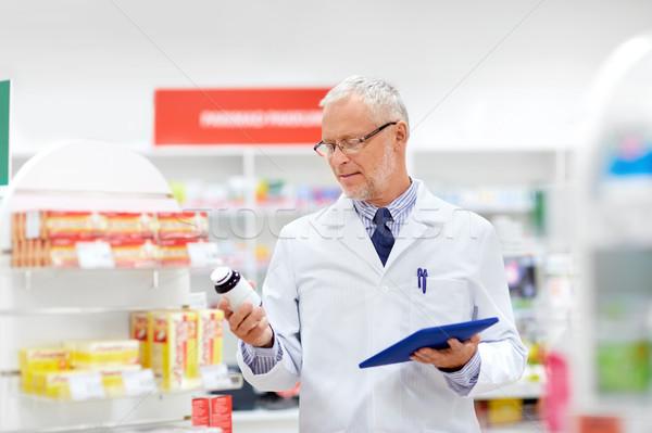 senior with tablet pc at pharmacy Stock photo © dolgachov