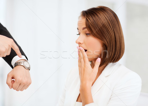 boss showing time to stressed businesswoman Stock photo © dolgachov