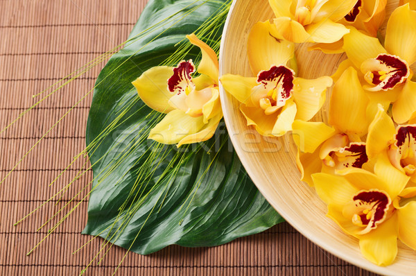 orchid flowers in bowl with green leaf on mat Stock photo © dolgachov