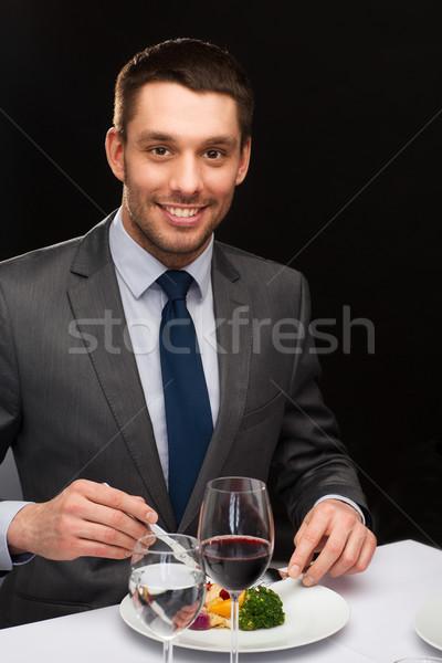 Uśmiechnięty człowiek jedzenie danie główne restauracji ludzi Zdjęcia stock © dolgachov