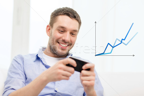 smiling man with smartphone at home Stock photo © dolgachov