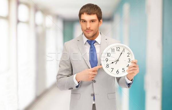 Bello imprenditore punta dito muro clock Foto d'archivio © dolgachov