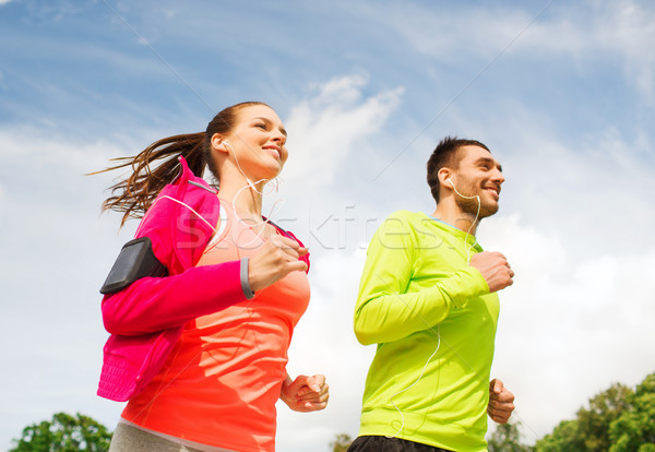smiling couple with earphones running outdoors Stock photo © dolgachov