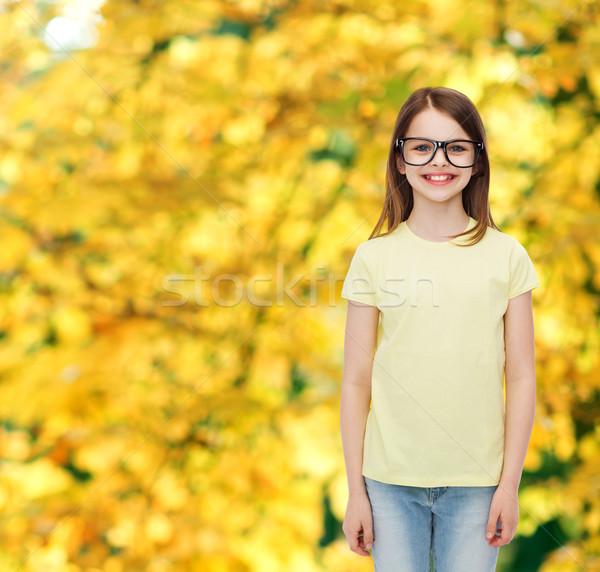 smiling cute little girl in black eyeglasses Stock photo © dolgachov