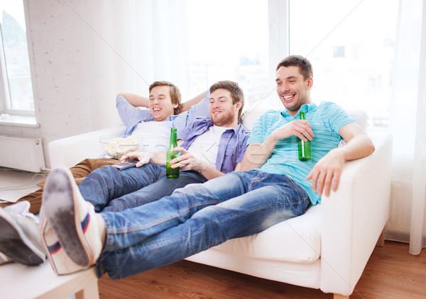 Stock photo: happy male friends with beer watching tv at home