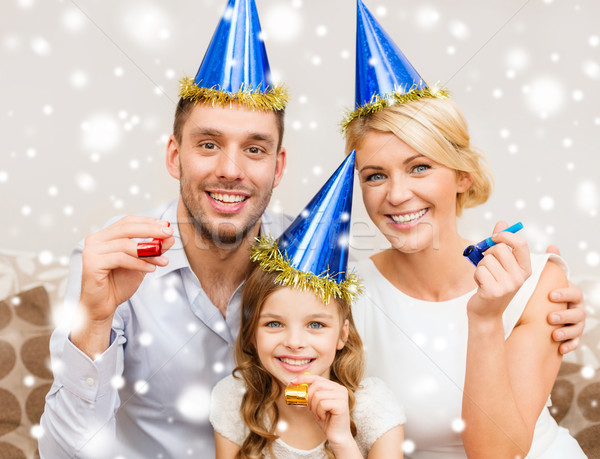 smiling family in party hats blowing favor horns Stock photo © dolgachov