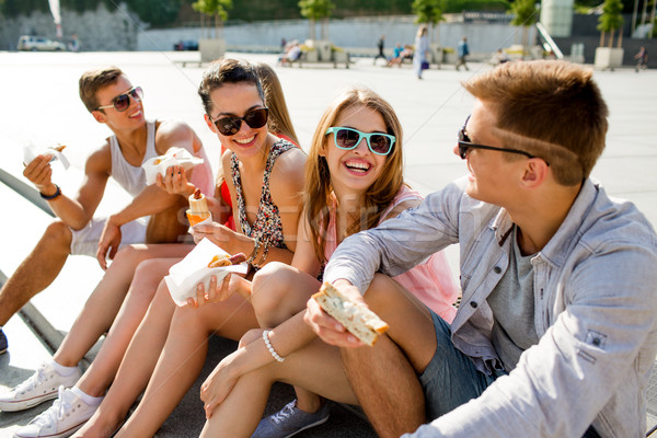 group of smiling friends sitting on city square Stock photo © dolgachov