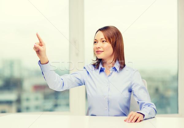 Сток-фото: улыбающаяся · женщина · указывая · что-то · мнимый · бизнеса · образование