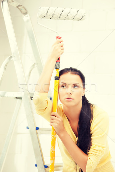 bored and tired young woman with paintroller Stock photo © dolgachov