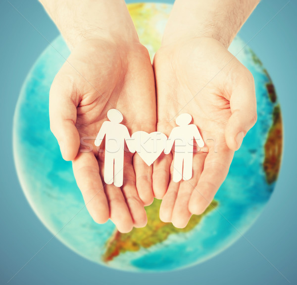 male hands with paper gay couple figures and globe Stock photo © dolgachov
