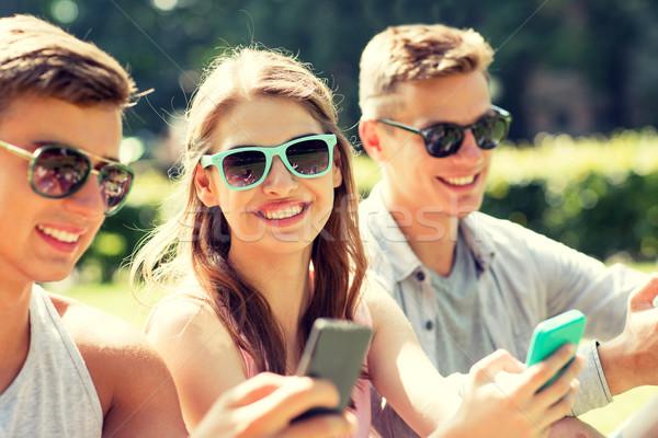 ストックフォト: 笑みを浮かべて · 友達 · スマートフォン · 座って · 公園 · 友情