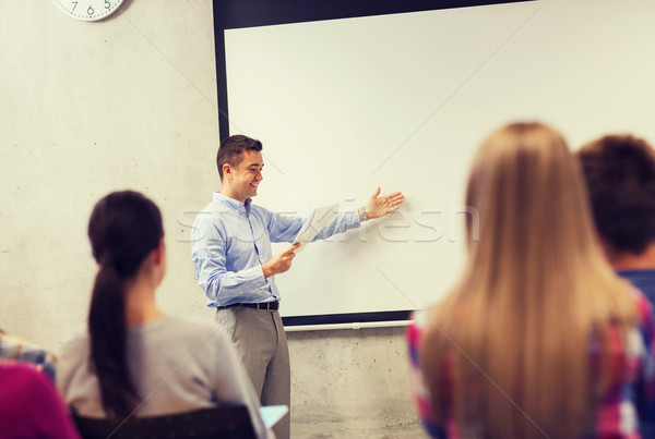 group of students and smiling teacher with notepad Stock photo © dolgachov