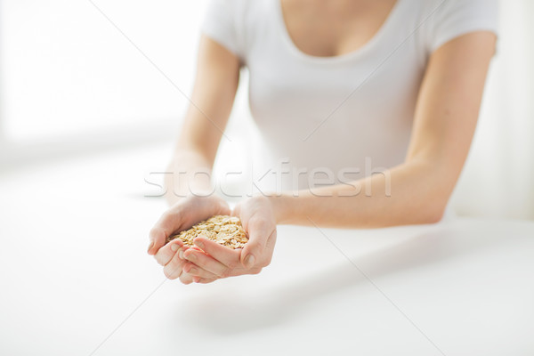 Stock photo: close up of woman hands holding oatmeal flakes